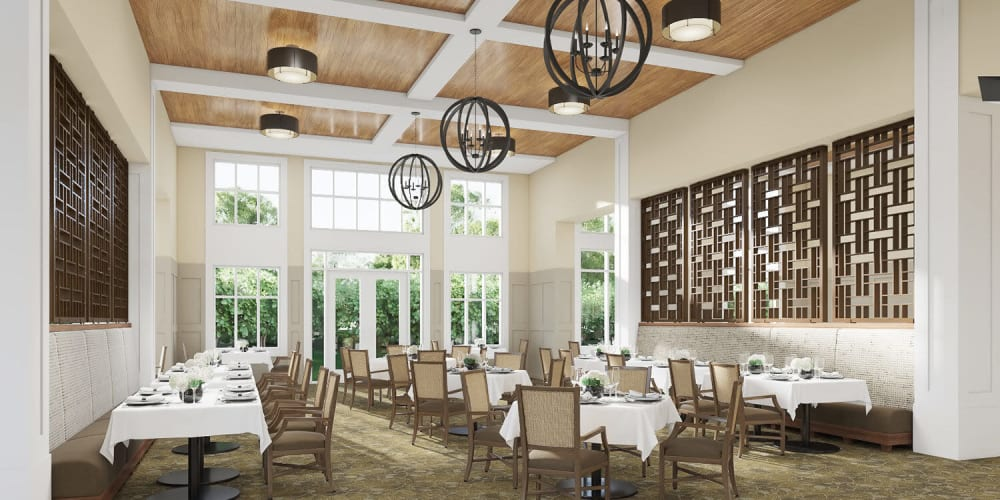 Brightly lit upscale senior dining room with modern chandelier and wood accents at The Springs at Sherwood in Sherwood, Oregon