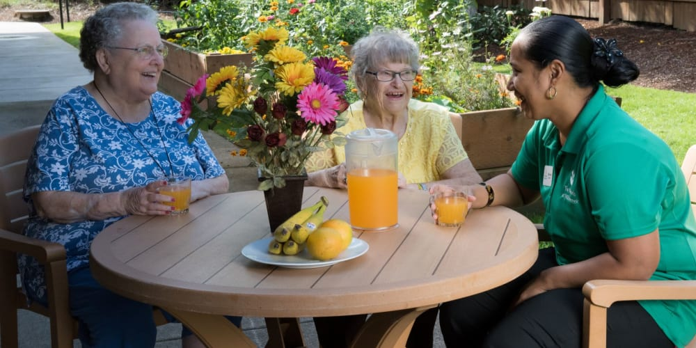 Two residents enjoying a beverage with an employee outside at wood table complete with sunflower centerpiece at The Springs at Willowcreek in Salem, Oregon
