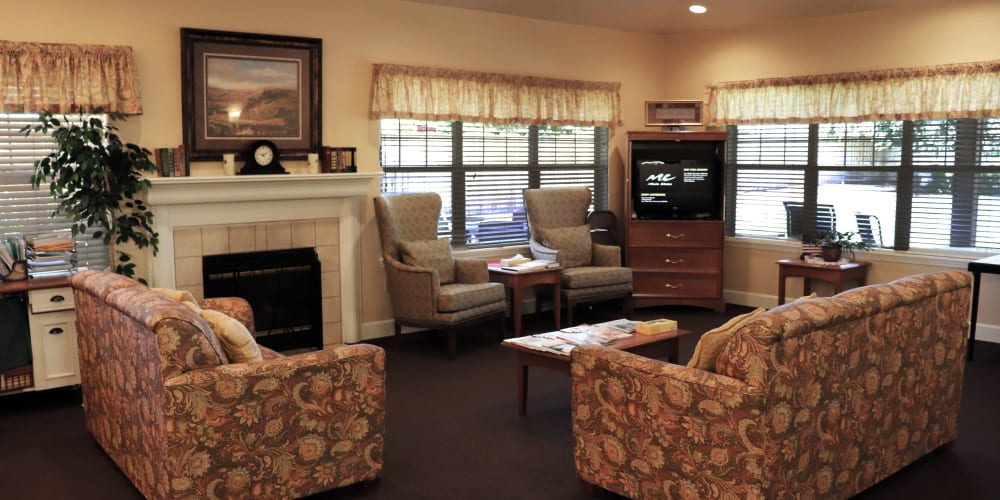 Communal sitting area complete with comfortable sofas, television set and fireplace at The Springs at Willowcreek in Salem, Oregon