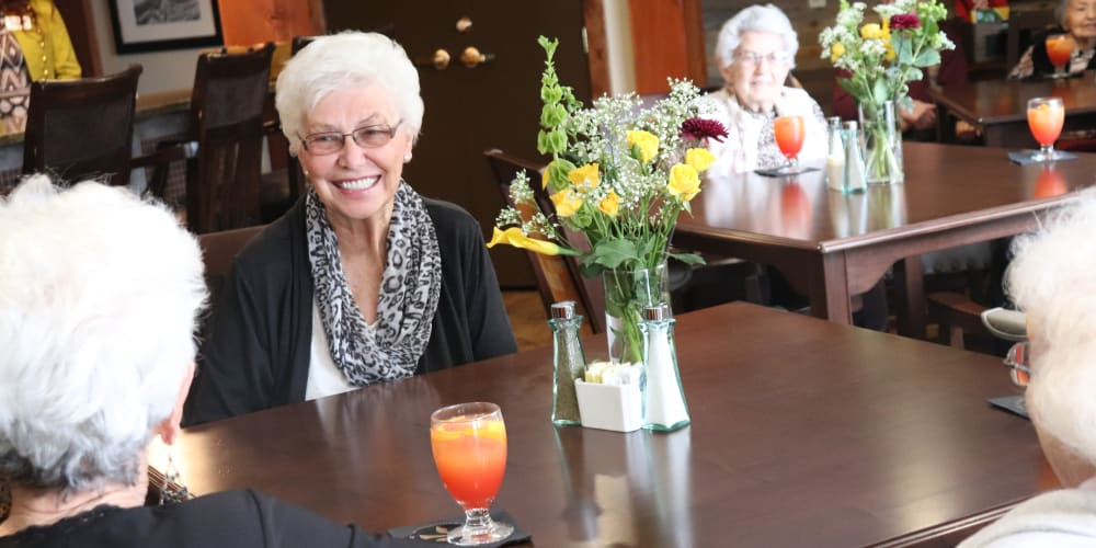 Resident smiling over a meal at The Springs at Butte in Butte, Montana