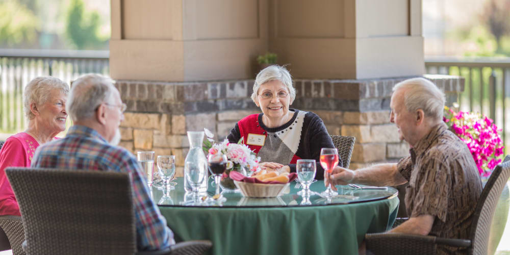 Smiling resident at a meal with friends at The Springs at Veranda Park in Medford, Oregon
