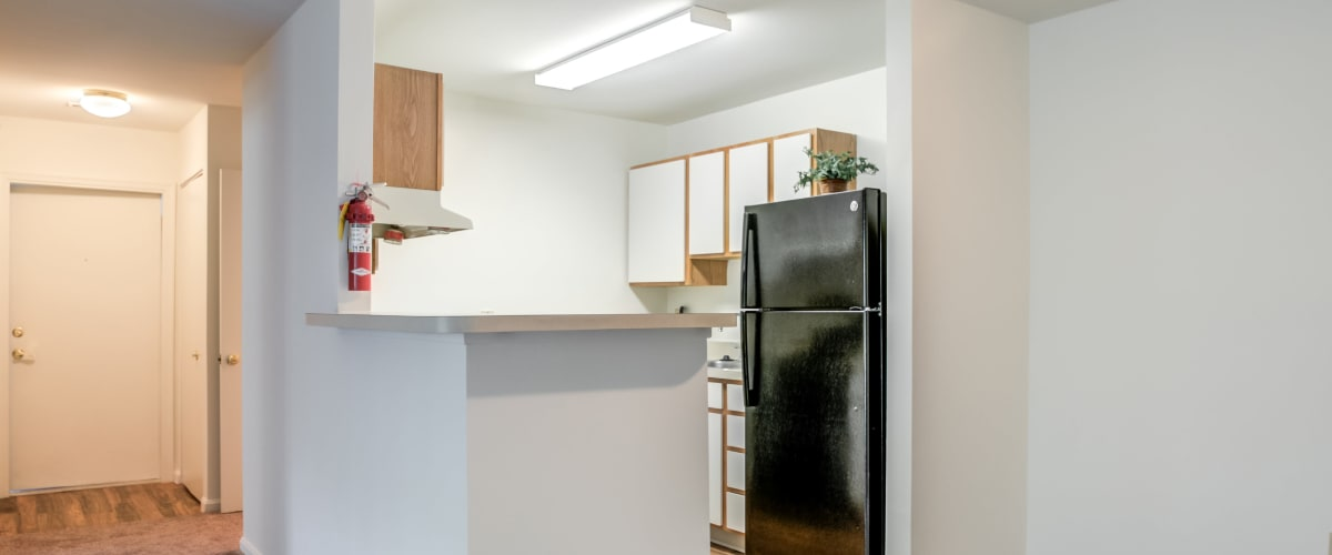A kitchen with a black fridge at The Vinings at Christiana in Newark, Delaware