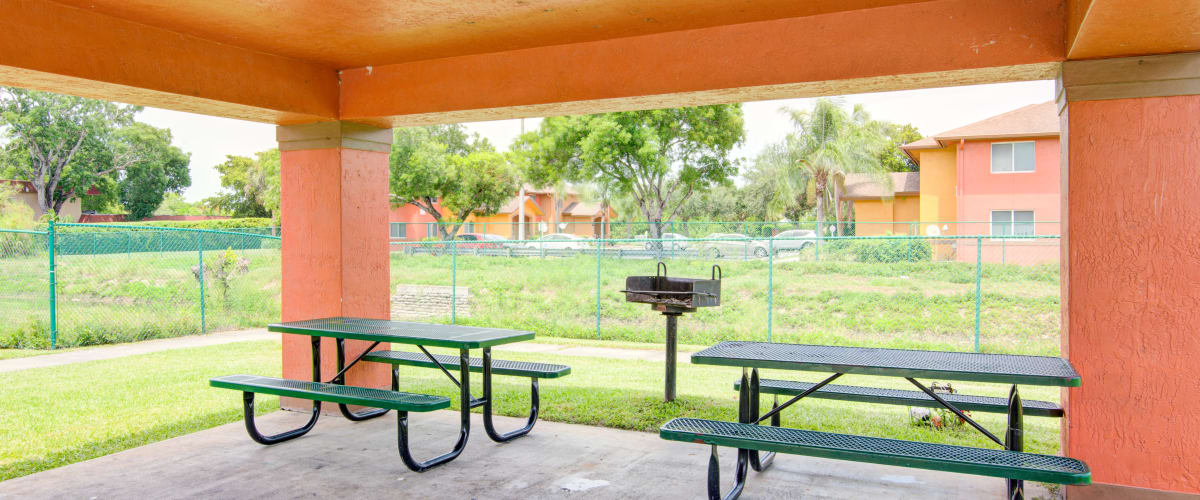 Covered picnic tables surrounded by a large grass lawn at Running Brook Apartments in Miami, Florida
