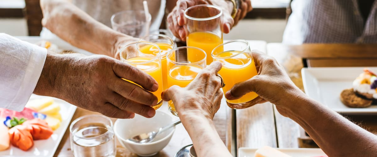 Seniors toasting with orange juice over breakfast