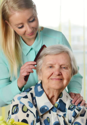 A caregiver brushes a resident's hair at Wyndham Court of Plano in Plano, Texas