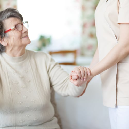 A nurse from At Home Care Group Oregon assisting a woman