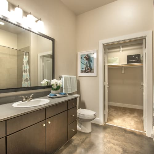 Granite countertop and a large vanity mirror in a model home's bathroom at Olympus at Ross in Dallas, Texas