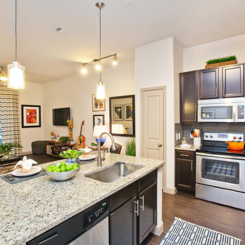 Gourmet kitchen with an island and granite countertops in a model home at Olympus Auburn Lakes in Spring, Texas