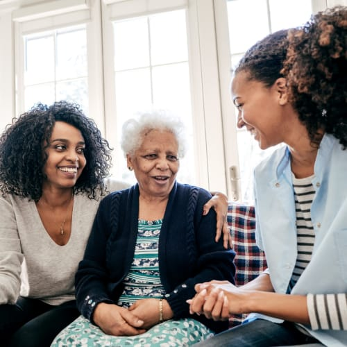 Resident talking to two younger women at a Ativo Senior Living community