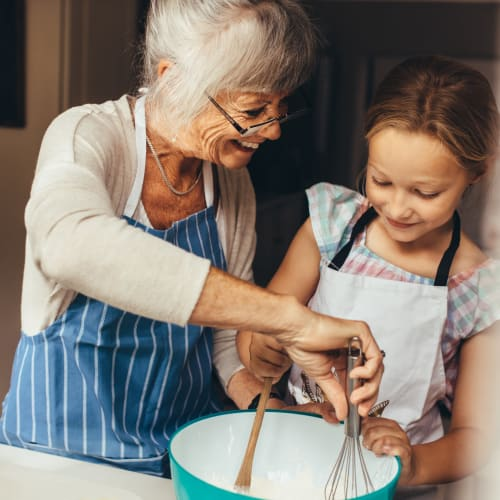 Resident mixing ingredients in a bowl with the help of a young child at a Ativo Senior Living community