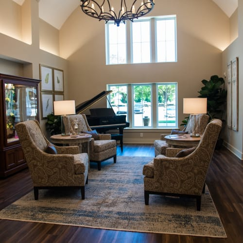 Brightly lit entrance lobby with comfortable armchairs and piano at Westminster Memory Care in Lexington, South Carolina
