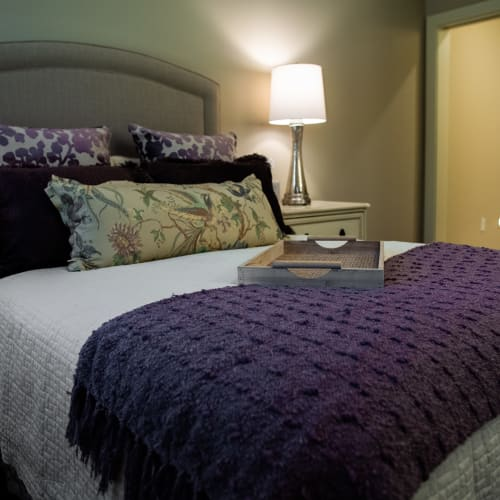 Comfortable resident bedroom with full-size bed and side table at Westminster Memory Care in Lexington, South Carolina