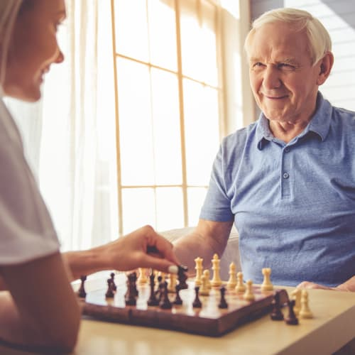 Resident and his daughter playing chess at Westminster Memory Care in Lexington, South Carolina