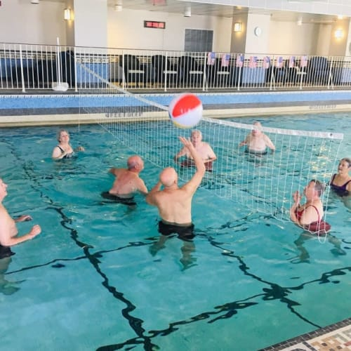 Seniors playing volleyball in an indoor pool at The Chamberlin in Hampton, Virginia