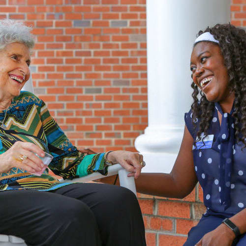 Resident and caregiver outside at The Crossings at Ironbridge in Chester, Virginia