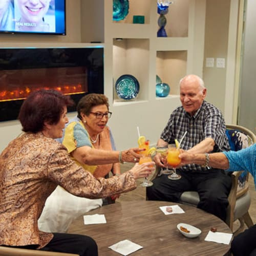 Residents relaxing with a toast in the lounge at The Crossings at Eastchase in Montgomery, Alabama