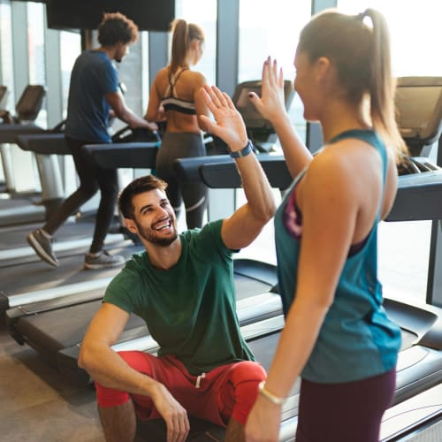 Residents high-fiving each other during a break from their workout in the fitness center at The Preserve at Greison Trail in Newnan, Georgia