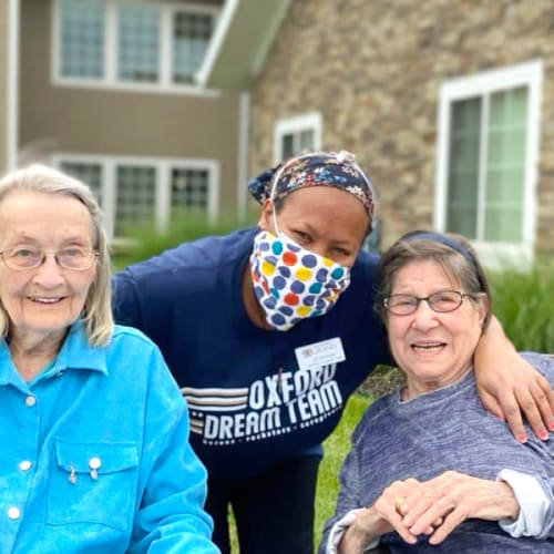 Smiling residents with a caregiver at The Oxford Grand Assisted Living & Memory Care in Kansas City, Missouri