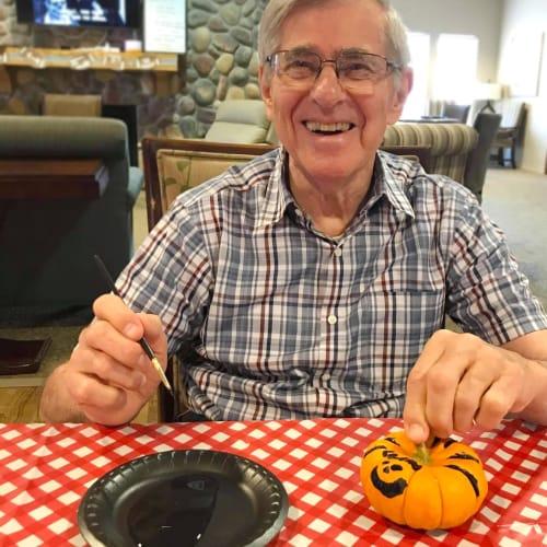 Man working on a pumpkin at Oxford Senior Living in Wichita, Kansas