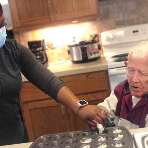 Team member with a resident in the kitchen at Oxford Glen Memory Care at Sachse in Sachse, Texas