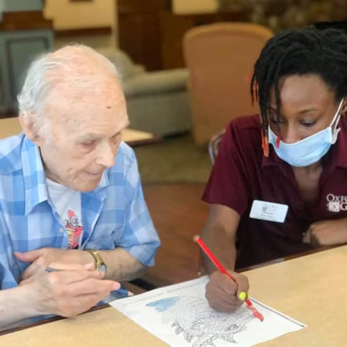 Resident coloring with caretaker at Oxford Glen Memory Care at Carrollton in Carrollton, Texas