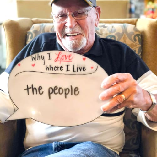 A resident holding a sign that says 'Why I love where I live: The people!' at a Oxford Senior Living community