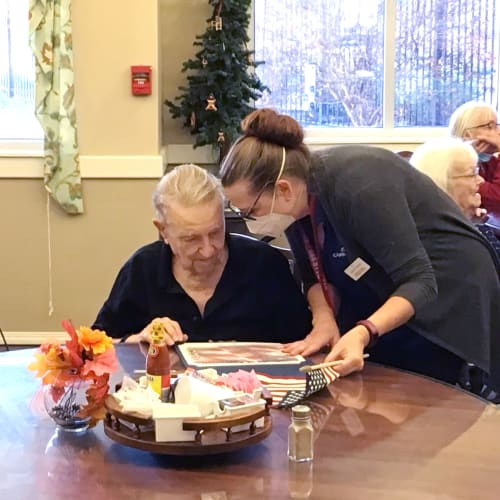 Resident talking to a masked caretaker in the dining hall at Canoe Brook Assisted Living & Memory Care in Catoosa, Oklahoma