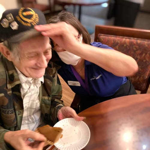 Resident putting a hat on a veteran at Canoe Brook Assisted Living in Broken Arrow, Oklahoma