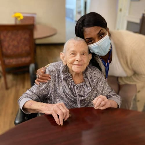 Masked caretaker with a seated resident at Canoe Brook Assisted Living in Broken Arrow, Oklahoma