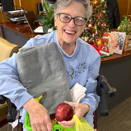 Happy resident with a gift basket at Canoe Brook Assisted Living in Ardmore, Oklahoma