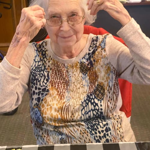 Resident putting on her glasses at Canoe Brook Assisted Living in Ardmore, Oklahoma