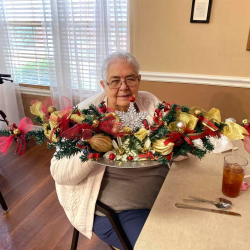 Resident sitting with a large bouquet of flowers at Canoe Brook Assisted Living in Duncan, Oklahoma