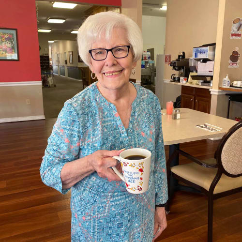 Resident in the dining room holding a cup of coffee at Canoe Brook Assisted Living in Duncan, Oklahoma