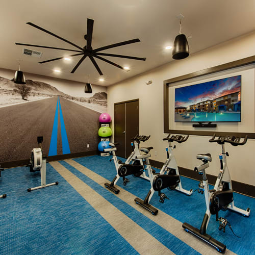 Modern fitness center with a flat-screen TV for workouts at Ocio Plaza Del Rio in Peoria, Arizona