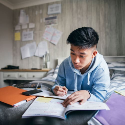 Student studying on his bed at home at University Park in Boca Raton, Florida