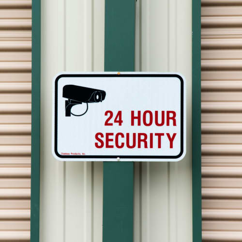 A sign for 24 hour security at Red Dot Storage in Evansville, Indiana