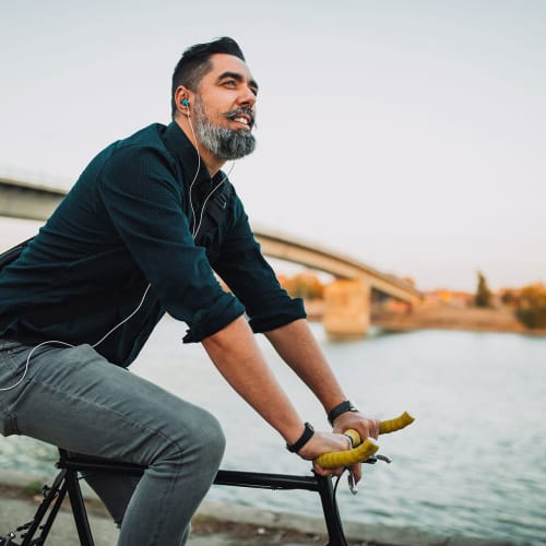 Well-groomed man listens to Nathanial Rateliff with in-ear headphones while riding a fixed-gear bicycle along the banks of the South Platte River near Hawthorne Hill Apartments in Thornton, Colorado