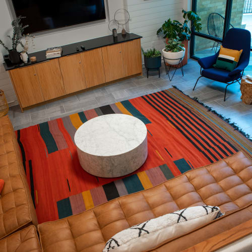 Living room interior featuring colorful area rug and brown leather couch seating in an apartment at Heritage Plaza in San Antonio, Texas