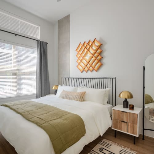 Bright white bedroom interior with queen size bed and orange accent art on the wall above the headboard in an apartment at Heritage Plaza in San Antonio, Texas