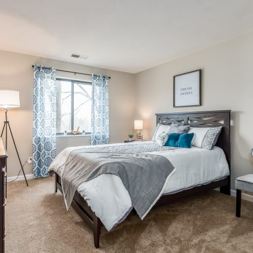 Model bedroom with carpet and a large window at Miamiview Apartments in Cleves, Ohio