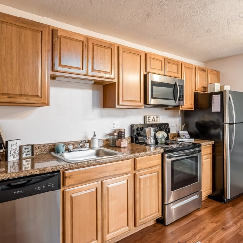 Kitchen with wood cabinets and appliances at Miamiview Apartments in Cleves, Ohio