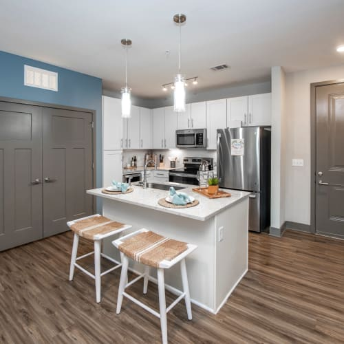 Gourmet kitchen with an island and granite countertops in a model home at Olympus Emerald Coast in Destin, Florida