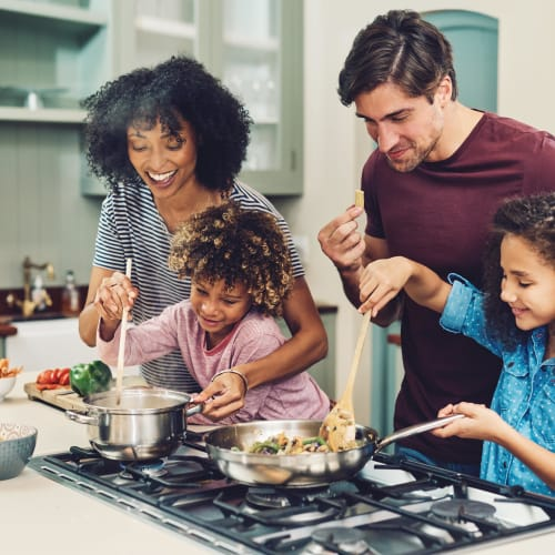 Resident family cooking up a fresh, delicious dinner in their new kitchen at Sedgefield in Marietta, Georgia