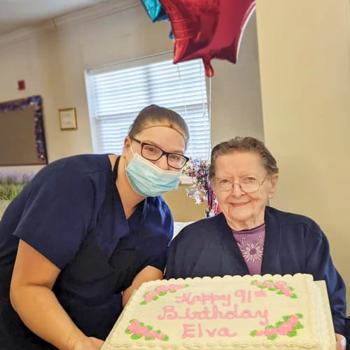 A resident and caregiver with a cake at Homestead House in Beatrice, Nebraska