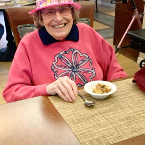 Smiling resident with fun hat and dessert at Saunders House in Wahoo, Nebraska
