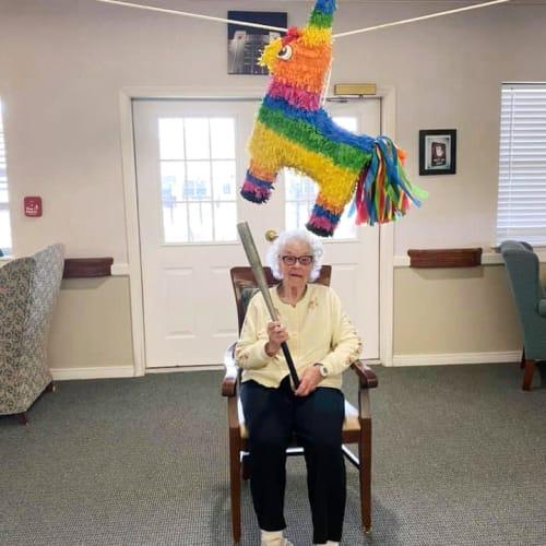 Resident swinging at piñata at Saunders House in Wahoo, Nebraska