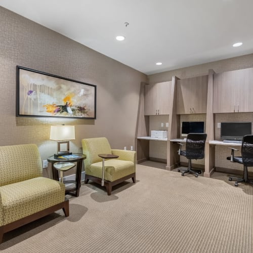 Business workstations with printer and cushioned desk chairs nearby of Marq at Crabtree in Raleigh, North Carolina