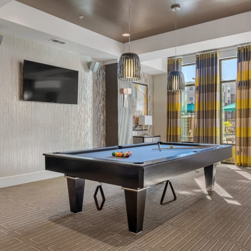 Pool table area with wall mounted television and speakers Marq at Crabtree in Raleigh, North Carolina