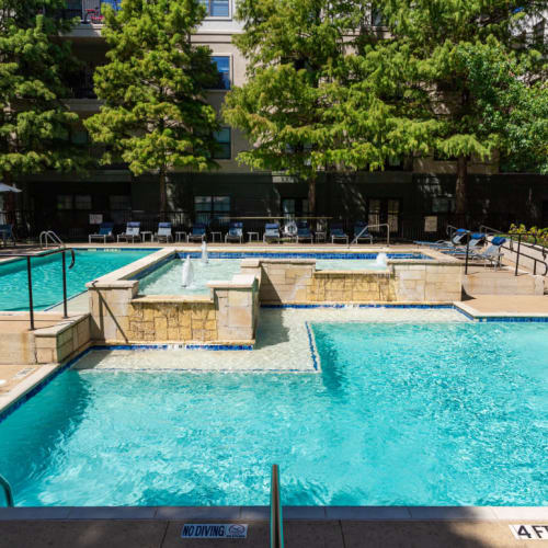 Water feature in center of sparkling pool with lounge chairs in back of Marquis at Texas Street in Dallas, Texas