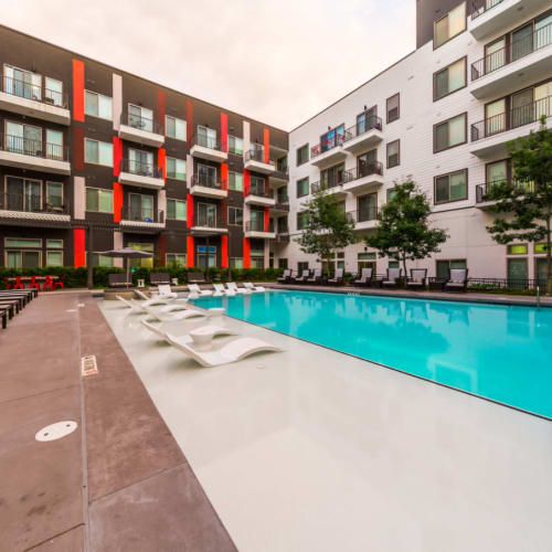 Resort style pool with in-water lounge chairs and tables at Marq on Burnet in Austin, Texas
